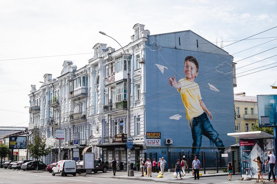 kiew streetart junge blau papierflugzeuge